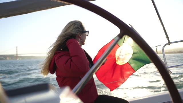 vídeos y material grabado en eventos de stock de un disparo a cámara lenta de una mujer rubia azotar su cabello en un bote - portugal