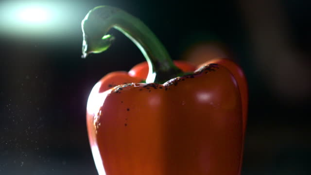 Slow motion shot of a blow torch scorching the skin of a red pepper.