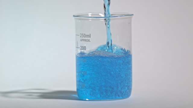 Slow motion shot of a blue liquid being poured into a laboratory glass beaker.