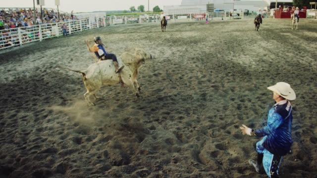 slow motion shot of a bull rider competing in a bull riding event before being thrown from the bull's back while the rodeo clown distracts the bull in a stadium full of people at sunset - bucking bronco stock videos & royalty-free footage