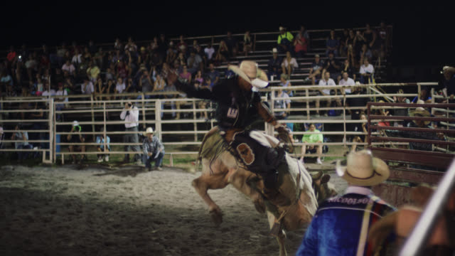 slow motion shot of a bull rider competing in a bull riding event before being thrown from the bull's back in a stadium full of people at night - rodeo stock videos & royalty-free footage