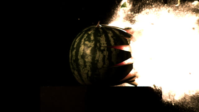 Slow motion shot of a bullet passing through a watermelon.