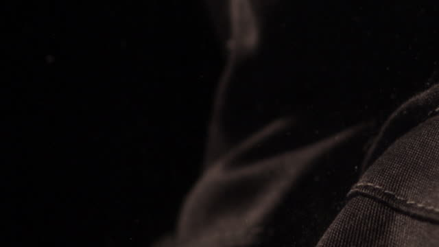 Slow motion shot of a bullet puncturing carbon fibre fabric.