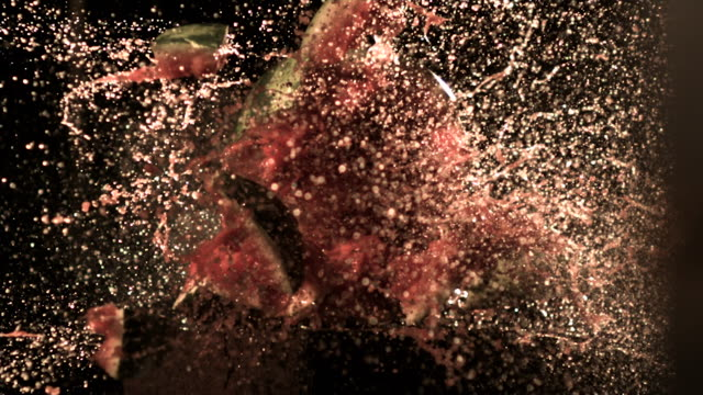 Slow motion shot of a bullet travelling through a watermelon.