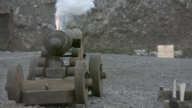slow motion shot of a cannon firing a cannon ball. - kanone stock-videos und b-roll-filmmaterial