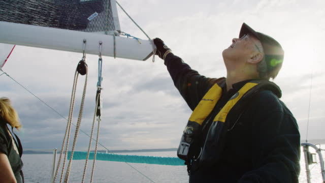 slow motion shot of a captain checking the mainsail while his small crew works on the deck of a sailboat in puget sound near seattle, washington - andare in barca a vela video stock e b–roll