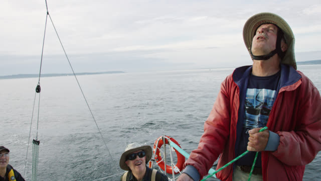 slow motion shot of a captain in his sixties pulling a rope tight in a winch on his sailboat on the puget sound in washington while his crew sits on the deck and laughs contentedly - mast sailing stock videos & royalty-free footage