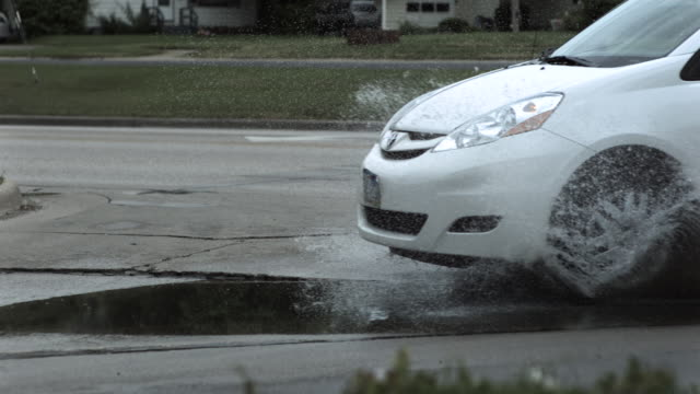 slow motion shot of a car driving through a puddle on a road. - puddle stock videos & royalty-free footage