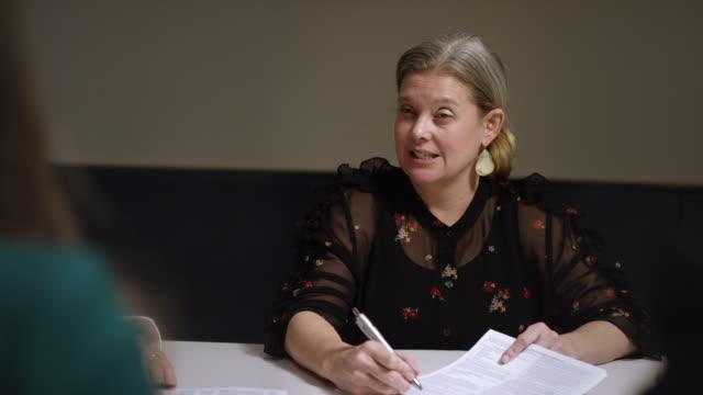 vídeos de stock, filmes e b-roll de tiro lento de uma mulher de negócio caucasiano em seus anos quarenta que discutem o documento com outro em uma tabela de conferência dentro - liderança