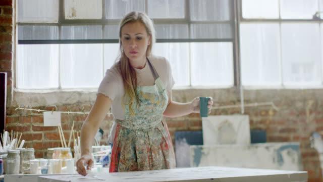zeitlupenaufnahme einer kaukasischen künstlerin in ihren vierzigern malerei auf einer leinwand mit einem malmesser in ihrem indoor art studio - one mature woman only stock-videos und b-roll-filmmaterial