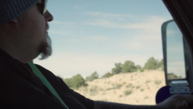 晴れた日にユタ州の高い砂漠で彼のセミトラックを運転ひげと入れ墨を持つ30代の白人男性トラック運転手のスローモーションショット - トラック運転手点の映像素材/bロール