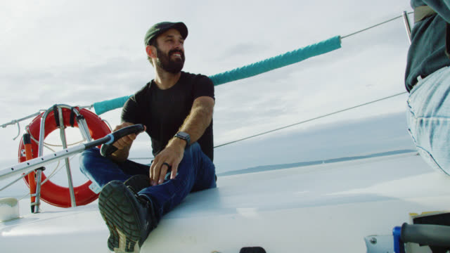 slow motion shot of a caucasian man in his thirties smiling as he sits on the deck of a sailboat and steers it with the tiller in puget sound in washington on a partly cloudy day - yacht stock videos & royalty-free footage
