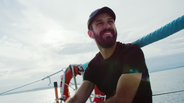 slow motion shot of a caucasian man in his thirties smiling as he sits on the deck of a sailboat in puget sound in washington on a partly cloudy day - yacht stock videos & royalty-free footage