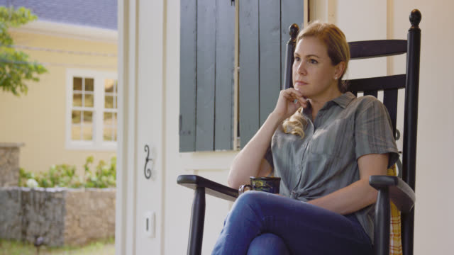 stockvideo's en b-roll-footage met slow motion shot van een kaukasische vrouw in haar veertigers schommelen in een schommelstoel met haar kopje koffie op haar outdoor veranda tijdens het denken en het bewonderen van de view - schommelen schommelstoel