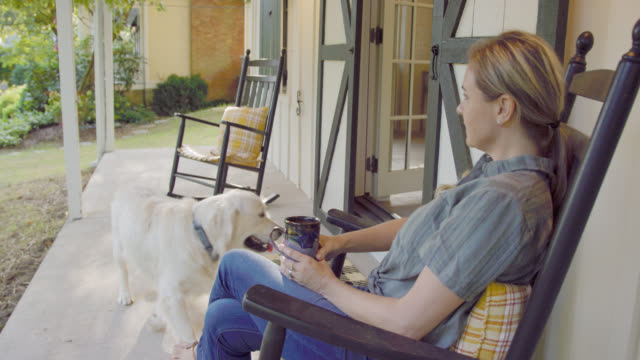 slow motion shot of a caucasian woman in her forties walking out double barn doors of her art studio and sitting on a porch rocking chair with a cup of coffee and her dog to admire the view outdoors - porch stock videos & royalty-free footage