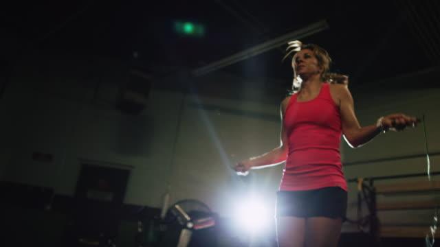 vídeos de stock, filmes e b-roll de tiro do movimento lento de uma mulher caucasiana em seus anos quarenta que desgastam a corda de salto da roupa dos esportes em uma ginástica interna - treino cruzado