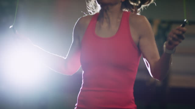 slow motion shot of a caucasian woman in her forties wearing sports clothing jumping rope in an indoor gym - rope stock videos & royalty-free footage