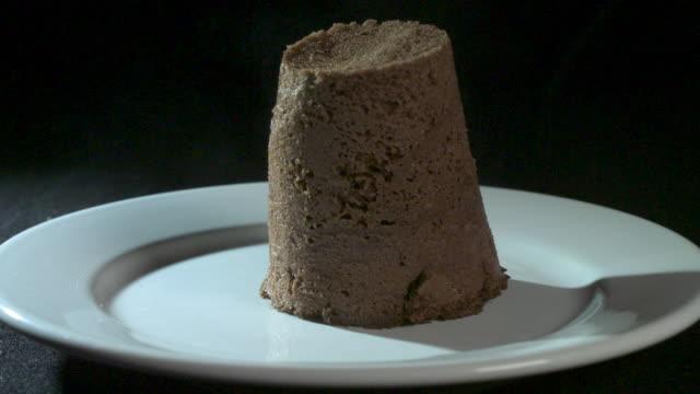 slow motion shot of a chocolate fondant cake falling onto a plate. - 盛り付け点の映像素材/bロール