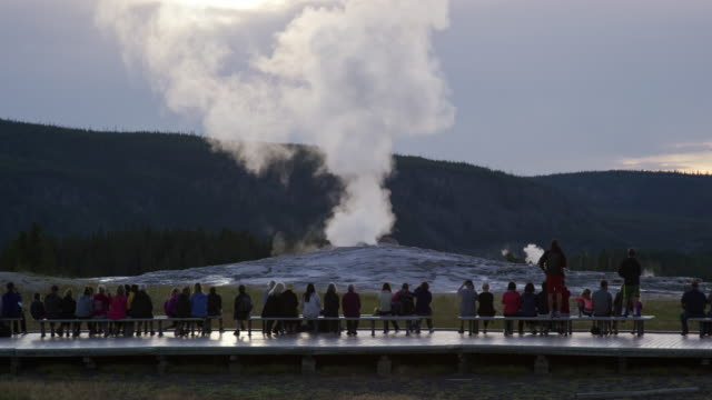 slow motion shot of a crowd of people waiting for old faithful geyser to erupt as it steams in yellowstone national park on an overcast day - old faithful stock videos & royalty-free footage