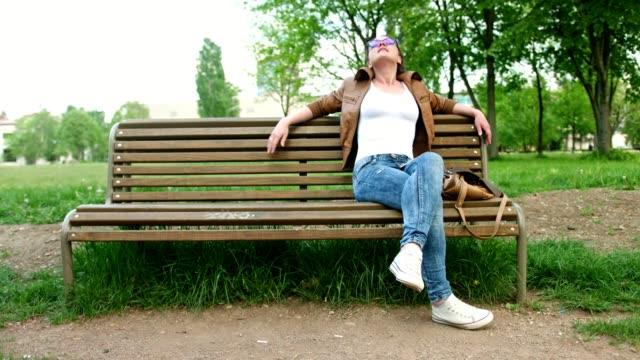 stockvideo's en b-roll-footage met slow-motion shot van een schattig meisje, zittend op een bankje in het park en genieten van het goede weer - bank zitmeubels