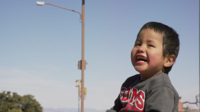 slow motion shot of a cute, two year-old native american (navajo) boy smiling and laughing outdoors - indigenous culture stock videos & royalty-free footage