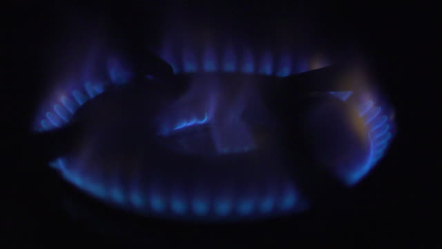 Slow motion shot of a gas burner igniting on a cooker hob.