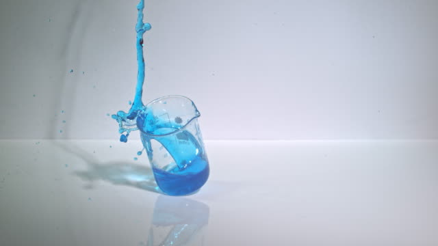 slow motion shot of a glass laboratory beaker containing a blue liquid being dropped onto a hard surface. - beaker stock videos & royalty-free footage