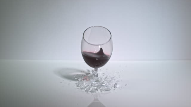 slow motion shot of a glass of red wine dropped onto a hard surface. - wine glass stock videos and b-roll footage