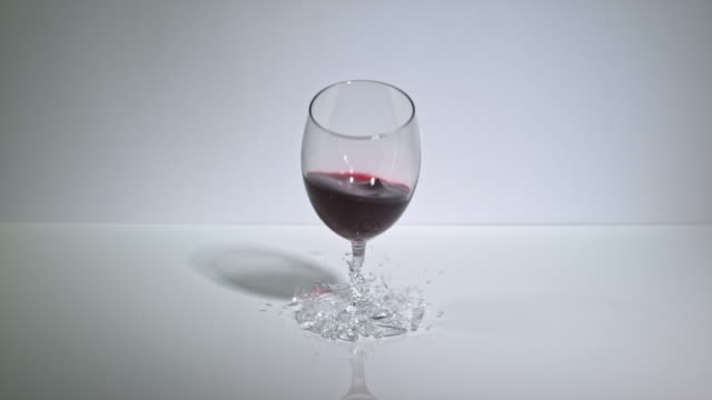 Slow motion shot of a glass of red wine smashing as it's dropped onto a hard surface.