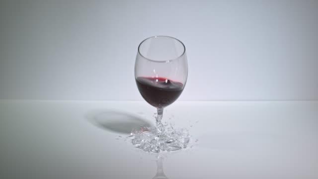 slow motion shot of a glass of red wine smashing as it's dropped onto a hard surface. - rött vin bildbanksvideor och videomaterial från bakom kulisserna
