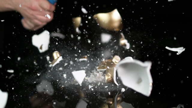 slow motion shot of a gold coloured piggy bank being smashed with a hammer. - pig stock videos & royalty-free footage