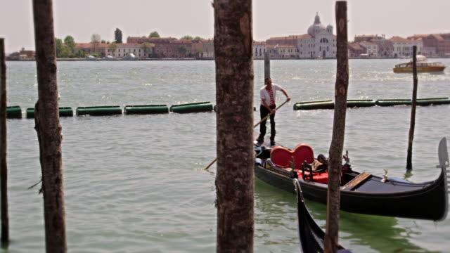 Slow motion shot of a gondolier docking his boat