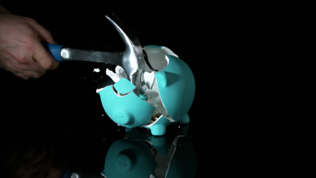 vidéos et rushes de slow motion shot of a green piggy bank being smashed with a hammer. - tirelire