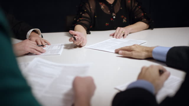 slow motion shot of a group of business women and men discussing paperwork at a conference table indoors - advice stock videos & royalty-free footage