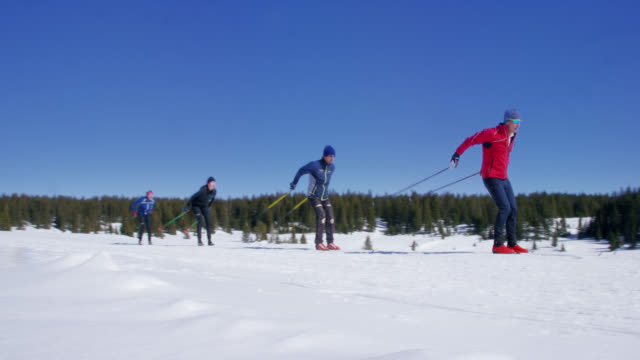 slow motion shot av en grupp av fyra vuxna längdskidåkning i en linje i bergen på en solig, vinterdag i colorado - längd bildbanksvideor och videomaterial från bakom kulisserna