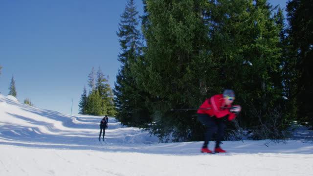 slow motion shot av en grupp av fyra vuxna tucking som de längdskidåkning i en linje ner ett berg på en solig, vinterdag i colorado - längd bildbanksvideor och videomaterial från bakom kulisserna