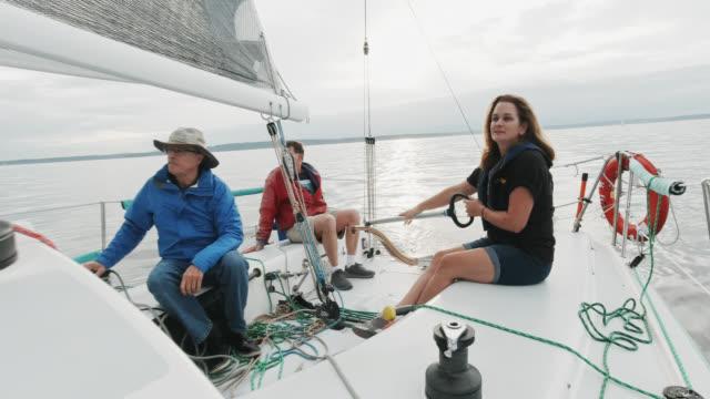 vidéos et rushes de slow motion shot d'un groupe de personnes assises et se relaxant sur le pont d'un voilier dans le bruit de puget près de seattle, washington - équipage de bateau