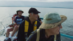Slow Motion Shot of a Group of People Sitting on the Deck of a Sailboat and Talking in Puget Sound near Seattle, Washington