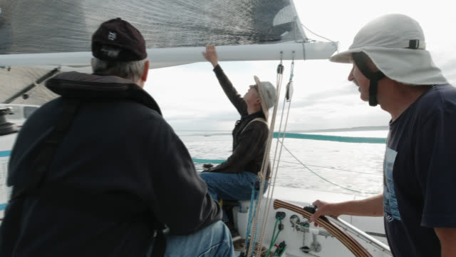 slow motion shot of a group of people sitting on the deck of a sailboat and talking in puget sound near seattle, washington - equipaggio video stock e b–roll