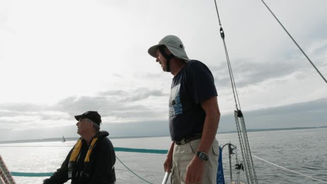 vídeos de stock, filmes e b-roll de tiro em câmera lenta de um grupo de pessoas sentadas no convés de um veleiro e falando em puget sound perto de seattle, washington - crew