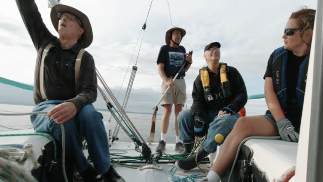 slow motion shot of a group of people sitting on the deck of a sailboat and talking in puget sound near seattle, washington - sailor stock videos & royalty-free footage