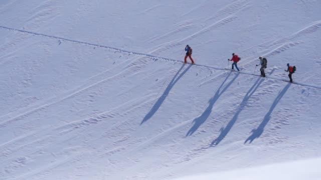 vidéos et rushes de coup de ralenti d'un groupe de skieurs randonnée à travers la neige - au loin