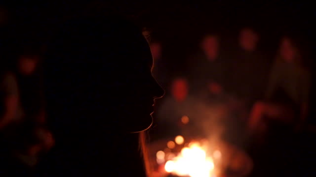 slow motion shot of a group of teens sitting near a campfire at night - heat stock videos & royalty-free footage