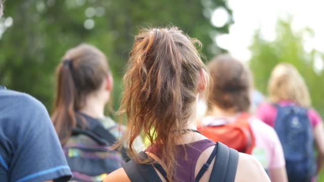 vídeos y material grabado en eventos de stock de slow motion shot of a group of young teens hiking in the woods from behind - 20 24 años
