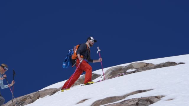 slow motion shot of a groups of skiers hiking along a mountain - sports clothing stock videos & royalty-free footage