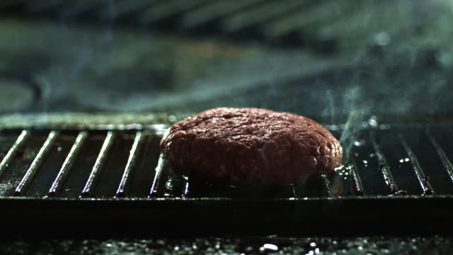 slow motion shot of a hamburger patty dropping onto a hot griddle. - グリルパン点の映像素材/bロール