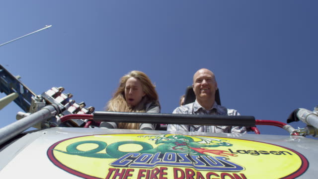 slow motion shot of a happy couple riding on a rollercoaster - rollercoaster stock videos & royalty-free footage