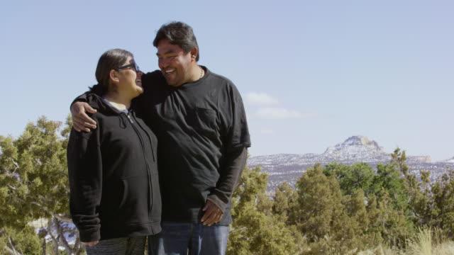 scatto al rallentatore di una coppia di nativi americani eterosessuali sulla trentina che si abbraccia, sorride e ride l'uno dell'altro in una giornata di sole all'aperto nello utah - nativo d'america video stock e b–roll