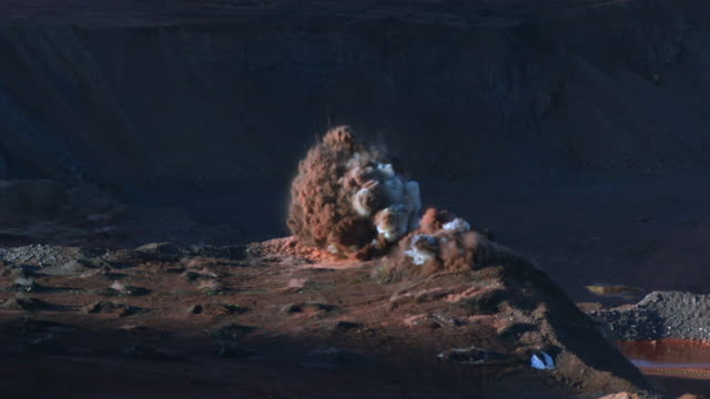 slow motion shot of a huge explosion at an iron min in south africa. - bergbau stock-videos und b-roll-filmmaterial