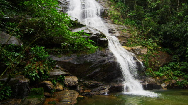Slow motion shot of a jungle waterfall cascading down a rocky outcropping into a pool of water.